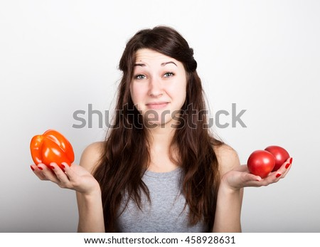 beautiful young woman eating an vegetables. holding a red pepper and tomato. healthy food - strong teeth and body concept.