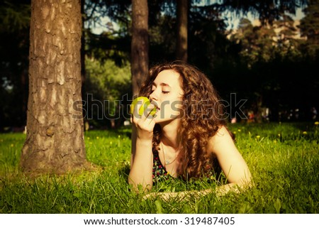 beautiful young woman eating apple outdoors in spring - stock photo