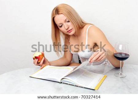 Beautiful young woman eating apple while reading book, with glass of red wine on the table - stock photo