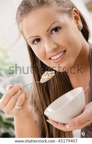 Beautiful young woman eating breakfast cereal. Selective focus on face.