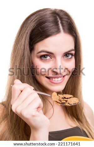 Beautiful young woman eating cereals over white background