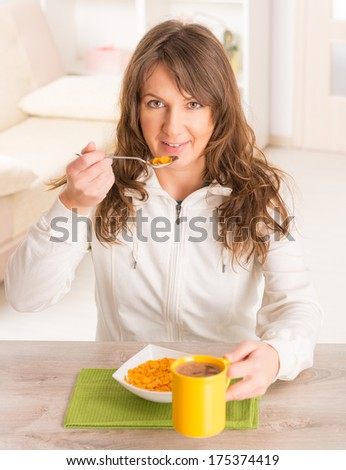 Beautiful young woman eating cornflakes and drinking coffee at home - stock photo