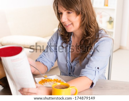 Beautiful young woman eating cornflakes and reading newspaper at home - stock photo