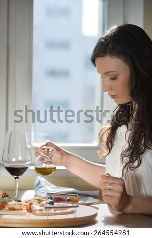 Beautiful young woman eating homemade pizza and drinking red wine at home - stock photo