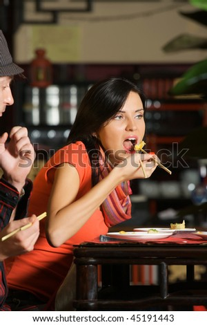 Beautiful young woman eating in Chinese restaurant. - stock photo