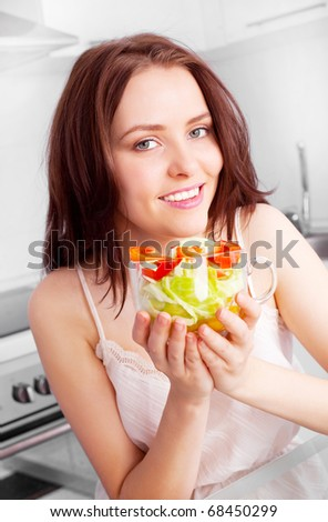 beautiful young woman eating salad in the kitchen  at home