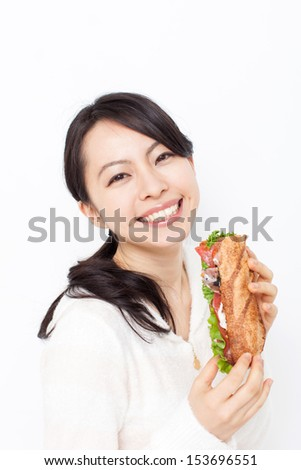 beautiful young woman eating sandwiches - stock photo