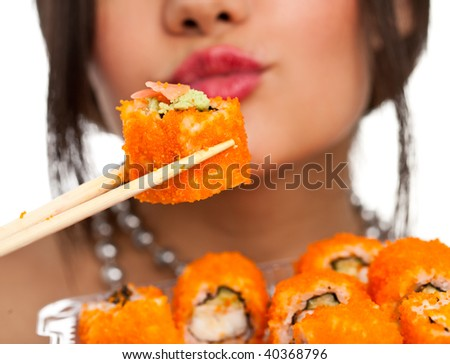 Beautiful young woman eating sushi california roll . Shallow depth of field, focus is on the sushi. isolated, studio.
