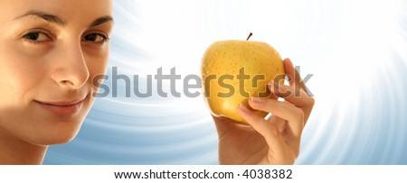 Beautiful young woman eating yellow apple.