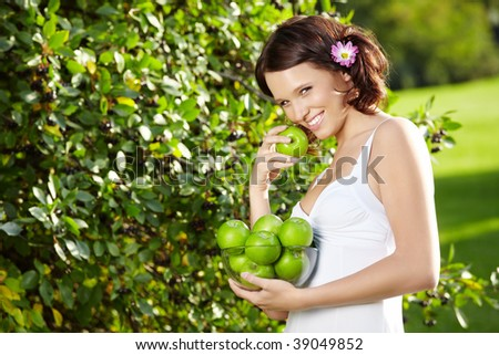 Beautiful young woman eats an apple in a summer garden, horizontally - stock photo