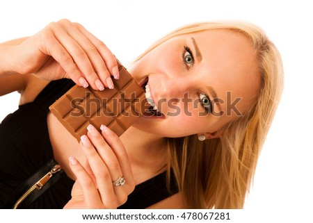 Beautiful young woman eats chocolate isolated over white background