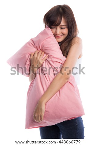 Beautiful young woman embracing pillow, wearing jeans and white shirt, isolated on white background