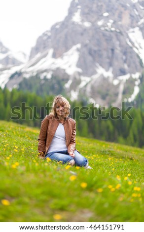 Beautiful young woman enjoy nature. Relaxing in flower garden in front of the Dolomites Alpine mountain.