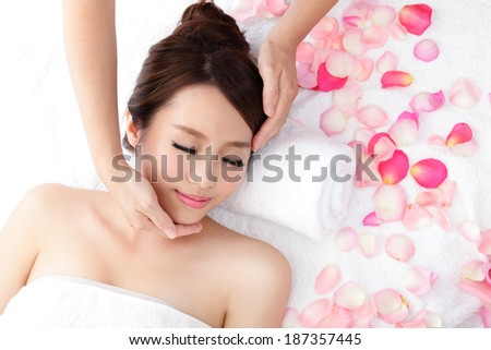 Beautiful young woman enjoy receiving face massage at spa with roses, she is very relaxed , asian beauty - stock photo