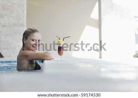 beautiful young woman enjoy sun and coctail dring relaxing and have fun at siwmming pool - stock photo
