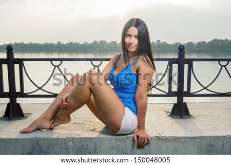 Beautiful young woman enjoy the breeze outdoor in a summer day sitting  near riverside one leg down - stock photo