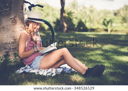 Beautiful young woman enjoying a book in the park - stock photo