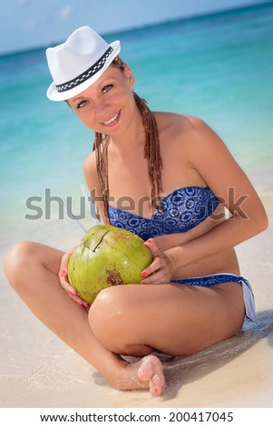 Beautiful young woman enjoying a cocktail in tropical paradise - stock photo