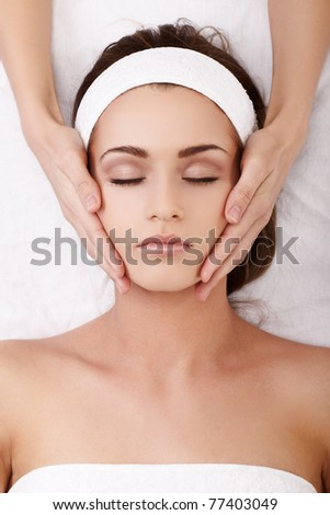 Beautiful young woman enjoying a facial massage - stock photo
