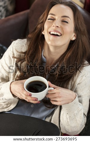 Beautiful young woman enjoying a fresh cup of coffee in a coffee shop