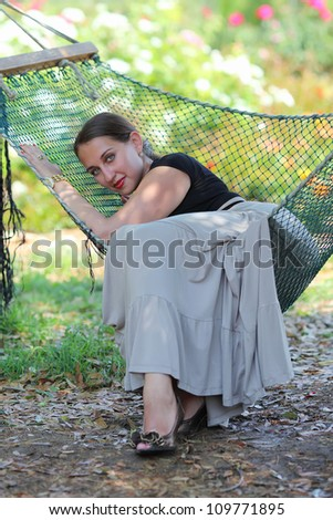 Beautiful young woman enjoying a hammock in the park