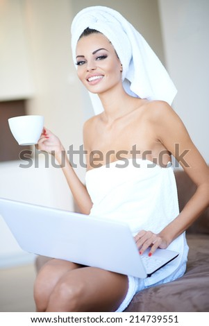 Beautiful young woman enjoying a relaxing morning sitting wrapped in clean white towels drinking a cup of coffee and working on her laptop computer - stock photo