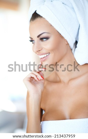 Beautiful young woman enjoying a spa treatment with her hair and body wrapped in fresh white towels smiling with pleasure as she looks to the left of the frame - stock photo