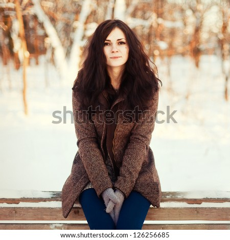 beautiful young woman enjoying a sunny winter day. Girl witting on a bench in cold park - stock photo