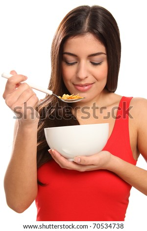Beautiful young woman enjoying breakfast cereal