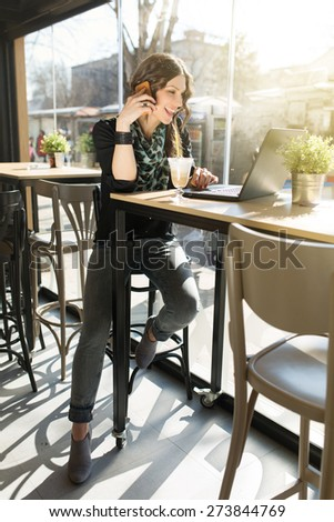 Beautiful young woman enjoying coffe, using laptop and talking on a cell phone, spending time in a city cafe. - stock photo