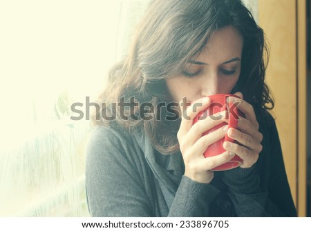 Beautiful young woman enjoying cup of coffee. Retro vintage instagram filter. - stock photo