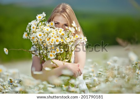 Beautiful young woman enjoying freedom on flower field - stock photo