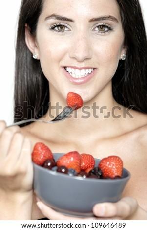 Beautiful young woman enjoying fresh fruit for breakfast - stock photo