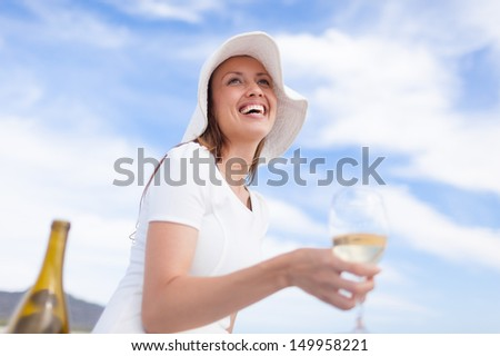 Beautiful young woman enjoying glass of wine on the beach - stock photo