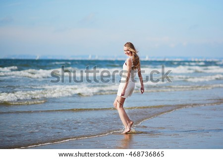 Beautiful young woman enjoying her vacation by ocean or sea, walking in water. People on sea vacation concept