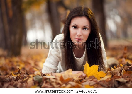 Beautiful young woman enjoying in the park at autumn
