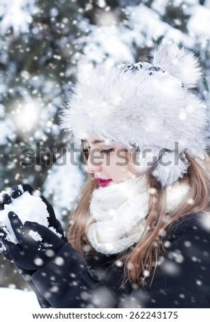 Beautiful young woman enjoying making a snowball. - stock photo