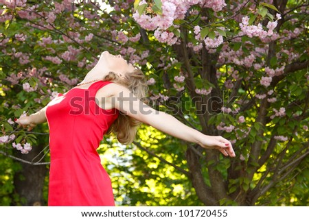 Beautiful young woman enjoying near blooming Japanese cherry tree. Spring outdoor