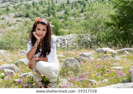 Beautiful young woman enjoying the beauty and wildflowers of the Morteratsch Glacier Valley along the hiking trail in the Bernina Mountain Range of the Bundner Alps in Switzerland. - stock photo