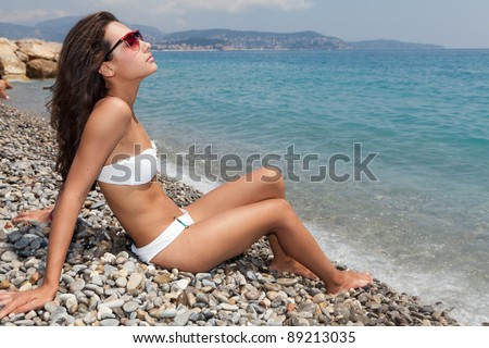 Beautiful young woman enjoying the Mediterranean beach shoreline in the French Riviera in Nice, France. - stock photo