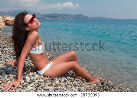 Beautiful young woman enjoying the Mediterranean Sea in Nice, France. - stock photo