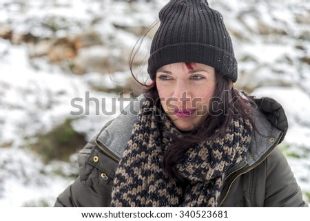 Beautiful young woman enjoying the snow on the mountains.