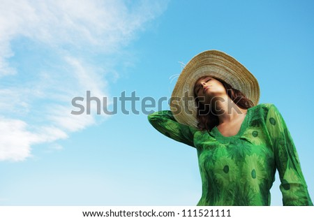 Beautiful young woman enjoying the sunny day against blue sky - stock photo