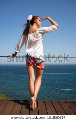 Beautiful young woman enjoying the view on the terrace. Seaside holidays.