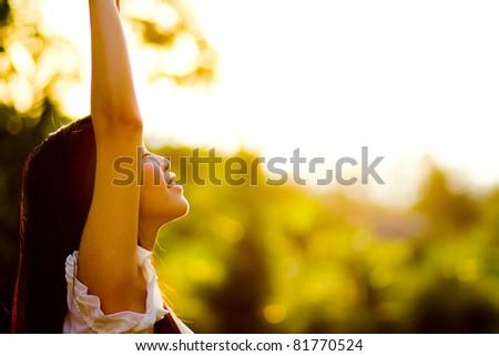 Beautiful young woman enjoys sun beams at summer park - stock photo