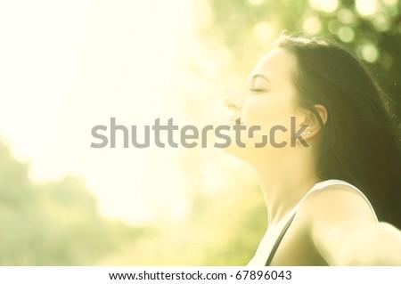 Beautiful young woman enjoys sun beams at summer park. Low contrast. - stock photo