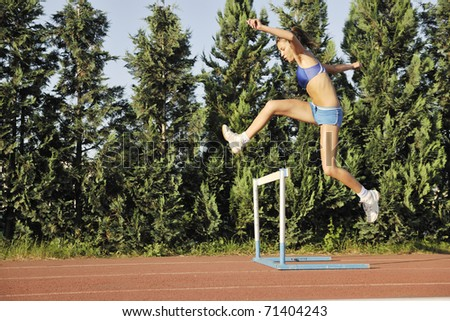 beautiful young woman exercise jogging and runing on athletic track on stadium at sunrise - stock photo