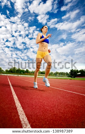 beautiful young woman exercise jogging and running on athletic track - stock photo