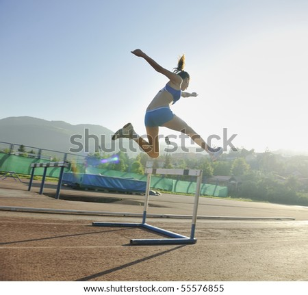 beautiful young woman exercise jogging and running on athletic track on stadium at sunrise