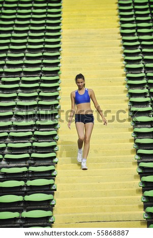 beautiful young woman exercise jogging and running on athletic track on stadium at sunrise - stock photo